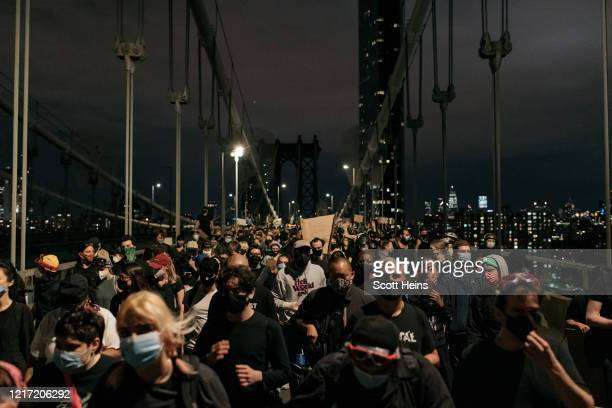 Protesters denouncing police brutality and systemic racism exit the Manhattan Bridge after being stopped by police for hours during a citywide curfew...