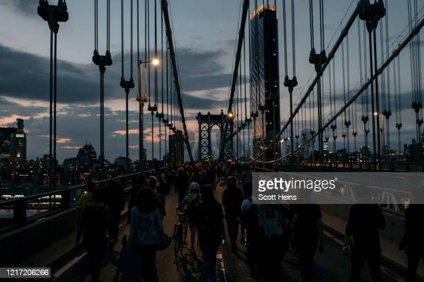 Protesters denouncing police brutality and systemic racism march over theManhattan Bridge after a citywide curfew in New York City. Days of protest,...