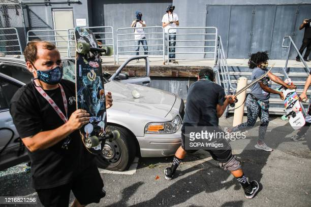 Protesters destroy a car with skateboards before setting the car on fire during a protest against the killing of George Floyd Protesters took to the...
