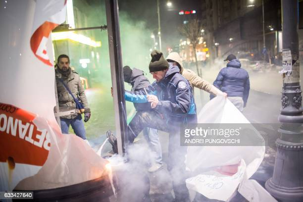 TOPSHOT Protesters destroy outdoor advertisment during a protest in front of the government headquarters against controversial decrees to pardon...