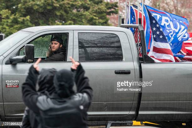 Protesters direct an obscene gesture to a driver with U.S. And Trump flags on March 28, 2021 in Salem, Oregon. The protesters clashed with occupants...