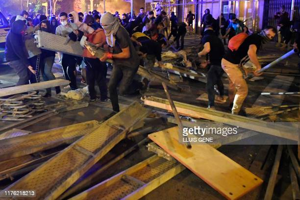 Protesters dismantle a scaffold to make barricades during a demonstration called by the local Republic Defence Committees in Barcelona on October 16...