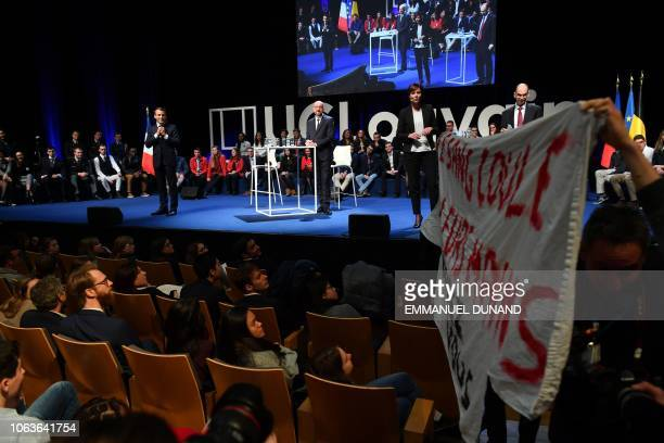 Protesters display a banner as French President Emmanuel Macron and Belgian Prime Minister Charles Michel take part in a conference at the UCL...