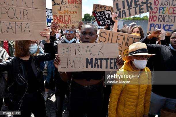 Protesters display anti racist and Black Lives Matter signs as protesters gather during a demonstration against racism and police brutality at Place...