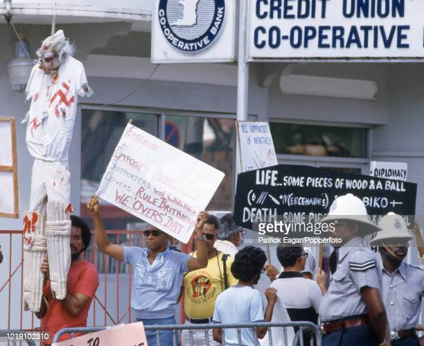 Protesters display anti-apartheid slogans on banners during the 2nd One Day International between West Indies and England at Queen's Park Oval, Port...
