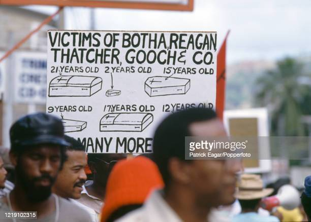 Protesters display antiapartheid slogans on banners during the 2nd One Day International between West Indies and England at Queen's Park Oval Port of...