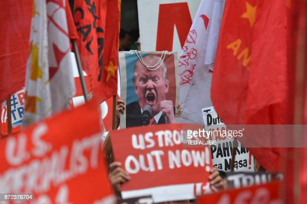 TOPSHOT Protesters display antiUS President Donald Trump placards along with his portrait during a rally near the US embassy ahead of the 31st...