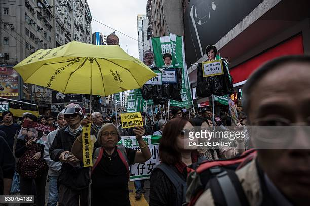Protesters display banners of chief executive candidates Woo Kwokhing and Regina Ip as well as Hong Kong Financial Secretary John Tsang and Chief...