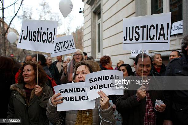Protesters display banners where it's written'public health' and 'justice' while doctors and patients celebrate the High court of justice of Madrid's...