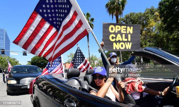 TOPSHOT Protesters display placards and US flags from their vehicle demanding the Stay at Home order to be lifted and the government to reopen the...