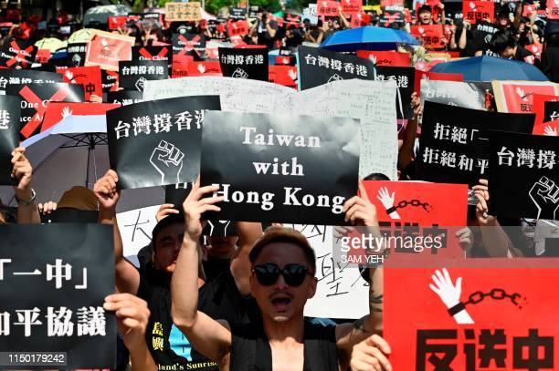 Protesters display placards during a demonstration in Taipei on June 16 in support of the continuing protests taking place in Hong Kong against a...