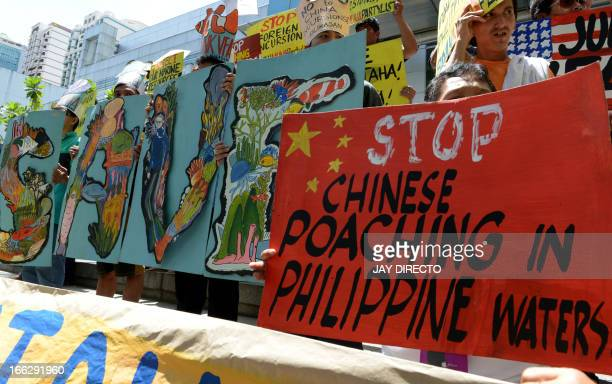 Protesters display placards during a rally in front of the Chinese consular office in Manila on April 11 against a Chinese fishing vessel that ran...