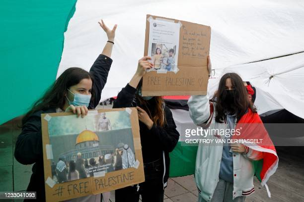 Protesters display placards under a Palestinian flag during a demonstration in solidarity with the Palestinian people on Republique square in Paris...