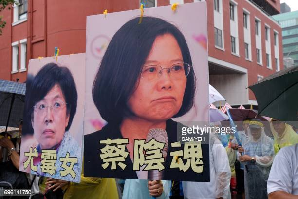 Protesters display portraits of Taiwan's president Tsai Ingwen and ruling Democratic Progressive Party legislator Yu Meinu during a demonstration...