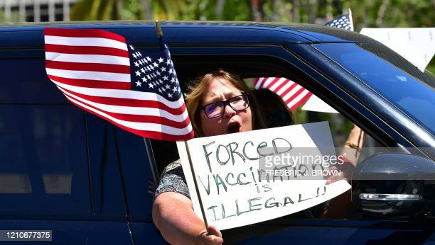 Protesters displaying placards and US flags cruise around City Hall in a motorcade demanding the Stay at Home order to be lifted and the government...
