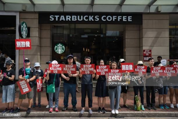Protesters displaying placards which reads Stop killing us during the demonstration in front of a Starbucks coffee shop Despite the Chief Executive...