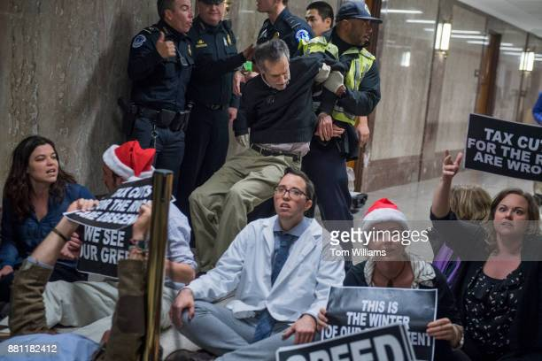 Protesters disrupt the Senate Budget Committee markup of the tax reform bill in Dirksen Building on November 28 2017