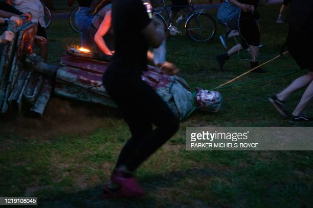 TOPSHOT Protesters drag a statue of Christopher Columbus to a nearby pond after pulling it down in Richmond Virginia June 9 2020 The protest was part...