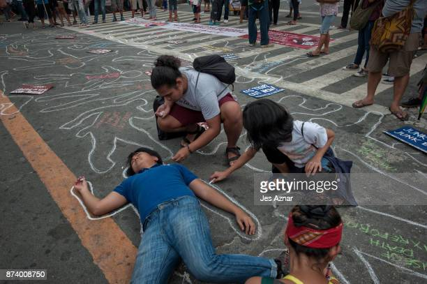 Protesters draw chalk outlines mimicking the thousands of killings happening under the Duterte presidency on November 14 2017 in Manila Philippines...