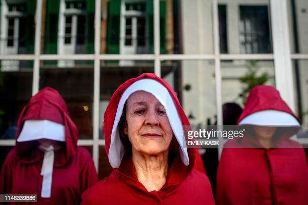Protesters dressed as characters from the series The Handmaid's Tale march down the French Quarter of New Orleans Louisiana on May 25 to protest the...