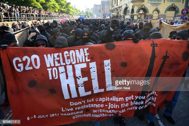 Protesters dressed in all black hold up a banner as they take part in the Welcome to Hell protest march on July 6 2017 in Hamburg Germany Leaders of...