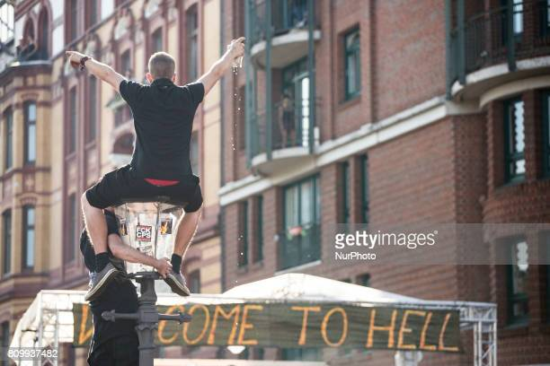 Protesters dressed in all black hold up a banner as they take part in the 'Welcome to Hell' protest march on July 6 2017 in Hamburg Germany Leaders...