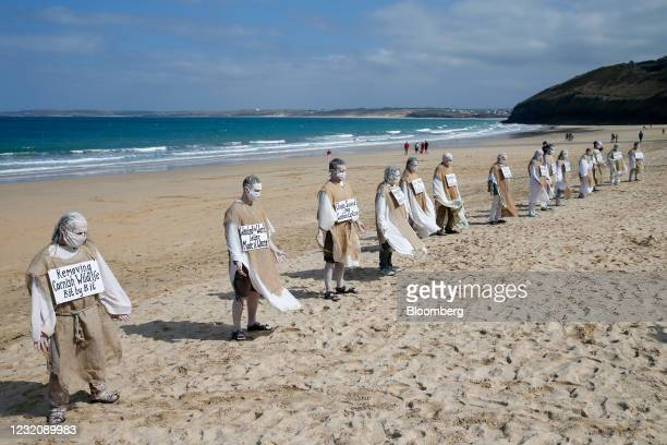 Protesters dressed in white and hessian sacks stand in line as they demonstrate against tree felling at the Carbis Bay Hotel development site on the...