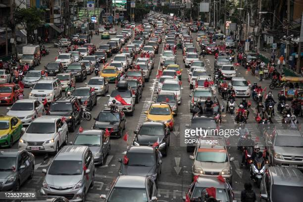 Protesters drive along the road while holding flags during the car mob rally. Anti-government protesters gathered at Asok intersection before they...