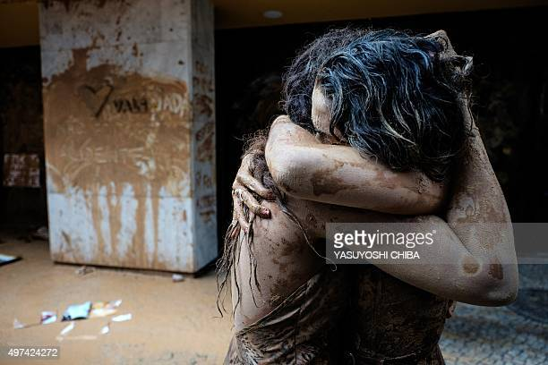 Protesters embrace after throwing muddy water on the façade of Brazilian mining company Vale headquarters in Rio de Janeiro Brazil on November 16...