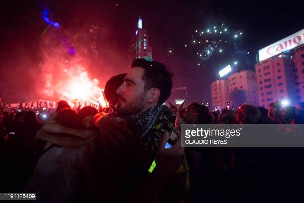Protesters embrace during a rally while enjoying the New Year's celebration in Santiago on December 31 2019 Chile has been rocked by months of...