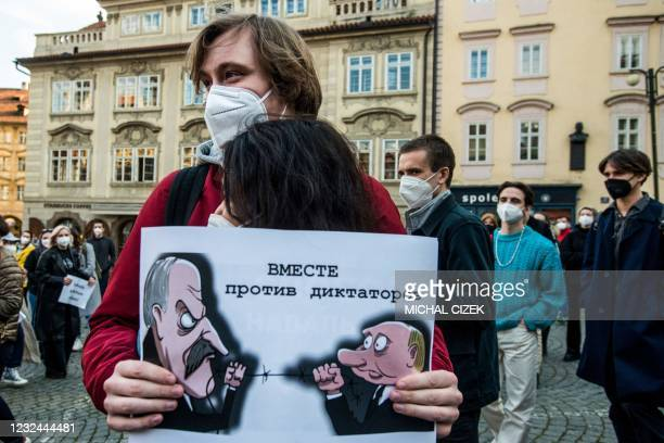 Protesters embrace while holding a poster depicting Russian President Vladimir Putin and Belarussian President Alexander Lukashenko take part in a...