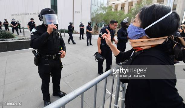 Protesters face off against police officers in front of the Los Angeles Police Department during a march over the death of George Floyd an unarmed...