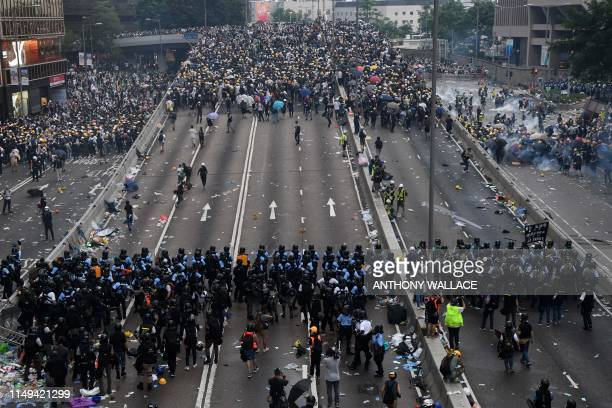 TOPSHOT Protesters face off with police after they fired tear gas during a rally against a controversial extradition law proposal outside the...