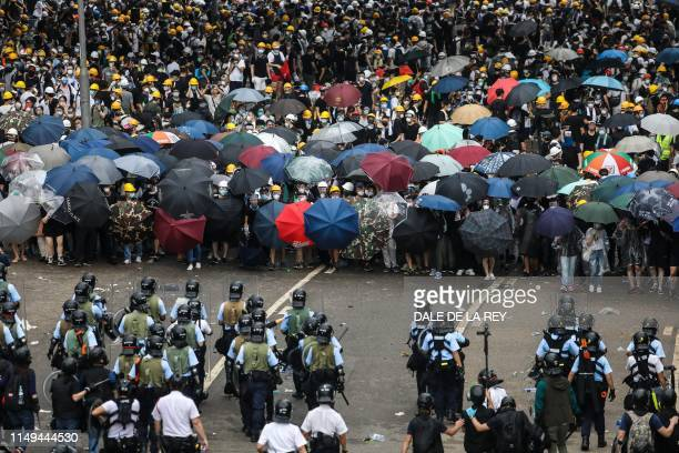 TOPSHOT Protesters face off with police during a rally against a controversial extradition law proposal outside the government headquarters in Hong...