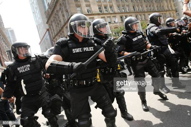 Protesters face off with riot police escorting censervative activists following a march in Boston against a planned 'Free Speech Rally' just one week...