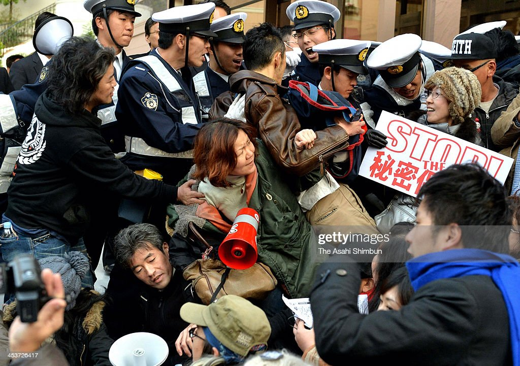 Protesters face off with the police officers at the public hearing site which is set up by the upper house committee, on December 4, 2013 in Saitama, Japan. The controversial bill was rammed through the Lower House and now in debate at the upper house.
