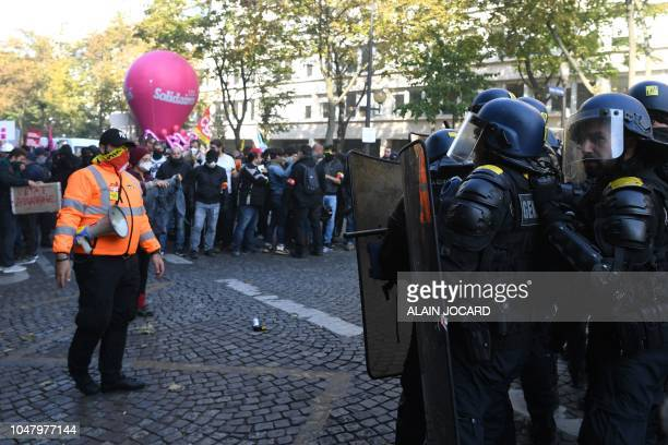 Protesters face riot police during a one-day nationwide ptotest over President Emmanuel Macron's policies on October 9, 2018 in Paris.
