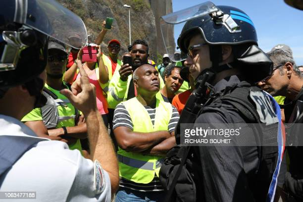 Protesters face riot police officers as they try to block a road on November 19 2018 in SaintDenisdelaReunion on the French overseas island of La...