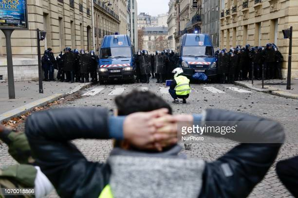 Protesters face riot police officers during the 'Yellow vests' demonstration on the ChampsElysees and other street on December 8 2018 in Paris France...
