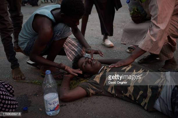 Protesters faints from tear gas and is revived moments before the security forces storm through the bus station June 30, 2019 in Khartoum, Sudan. The...