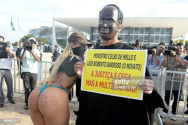 Protesters fancy dressed as the president of Brazil's Supreme Court Joaquim Barbosa and popular singer Bandida take part in a protest against the...