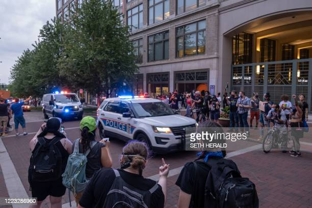 Protesters film with their cell phones and yell at Columbus Police Department officers after they towed a medic's car near City Hall during an...