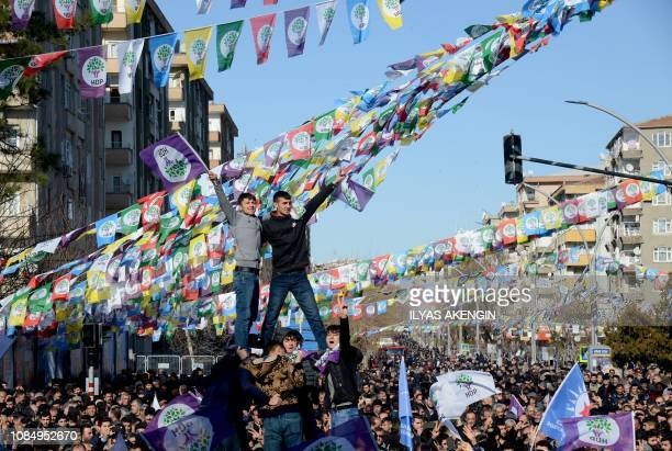 Protesters flash the Vsign for 'victory' during a rally in the Kurdishmajority city of Diyarbakir southeastern Turkey on January 19 in support of a...