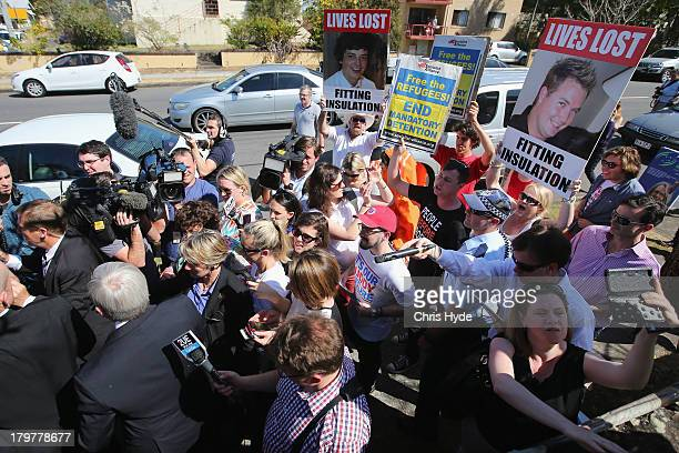 Protesters follow Australian Prime Minister Kevin Rudd as he leaves St Paul's Church in the seat of Griffith on September 7 2013 in Brisbane...
