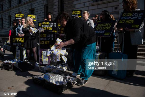 Protesters for a change in Northern Irish law on abortion remove petitions from suitcases outside the Northern Ireland Office at Parliament Square on...