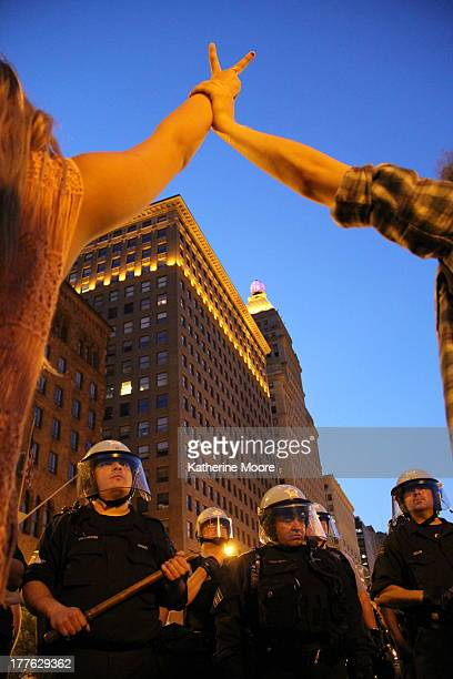 Protesters form peace signs as they face police in riot gear at Congress and Michigan streets. The Chicago protest coincided with the NATO summit.
