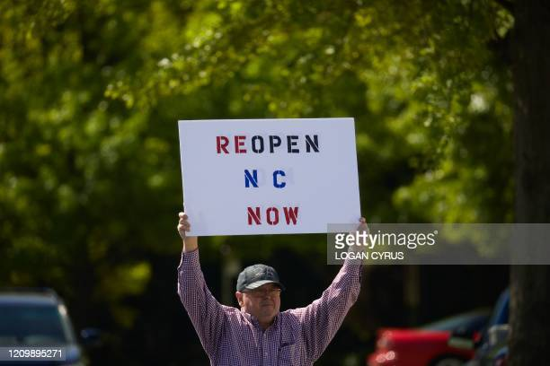 TOPSHOT Protesters from a grassroots organization called REOPEN NC protests the North Carolina coronavirus lockdown at a parking lot adjacent to the...