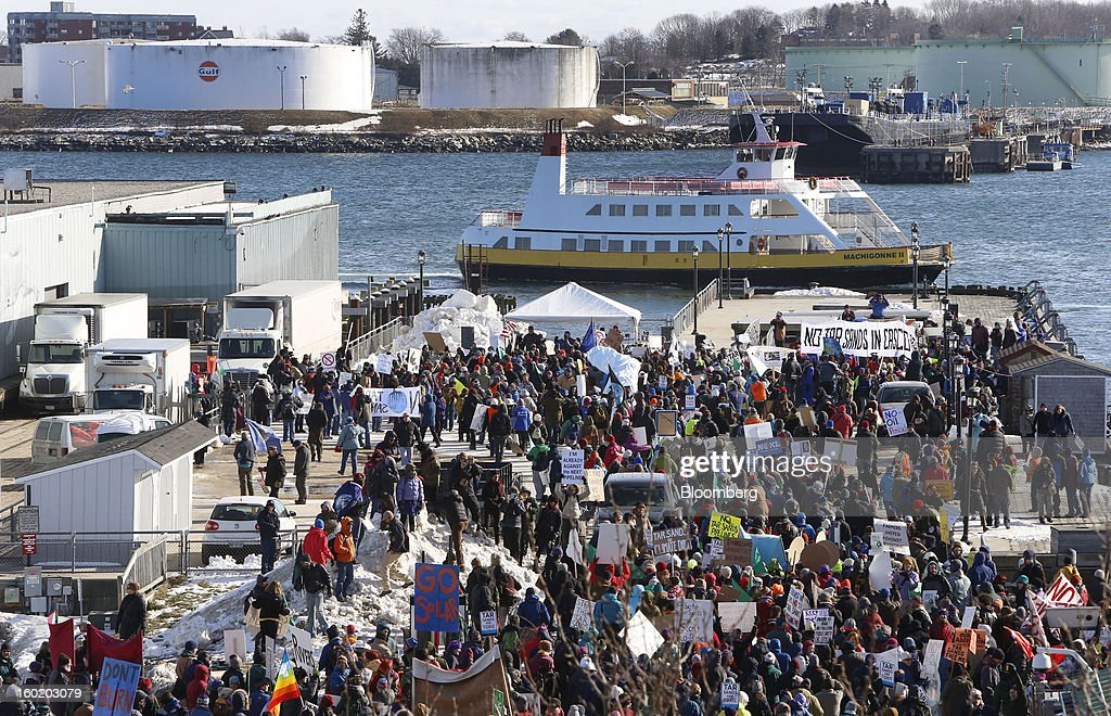 Protesters from across New England hold signs during a rally against the possibility of so-called tar sands oil being piped in from Montreal, at the waterfront of Portland, Maine, U.S., on Saturday, Jan. 26, 2013. The Associated Press reported that environmental groups say plans are in the works to bring oil by pipeline from western Canada to Montreal and then to Portland. Critics say tar sands, or oil sands, oil is so corrosive, acidic and thick that it's more likely to spill than conventional crude oil and that would put rivers, lakes and streams at risk in Maine, New Hampshire and Vermont, according to AP. Photographer: Bizuayehu Tesfaye/Bloomberg via Getty Images