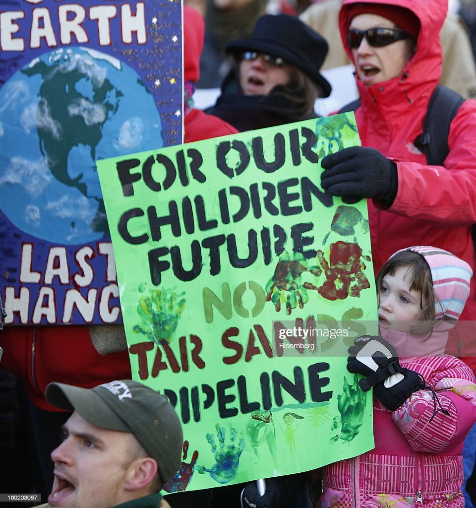 Protesters from across New England hold signs during a rally against the possibility of so-called tar sands oil being piped in from Montreal, in Portland, Maine, U.S., on Saturday, Jan. 26, 2013. The Associated Press reported that environmental groups say plans are in the works to bring oil by pipeline from western Canada to Montreal and then to Portland. Critics say tar sands, or oil sands, oil is so corrosive, acidic and thick that it's more likely to spill than conventional crude oil and that would put rivers, lakes and streams at risk in Maine, New Hampshire and Vermont, according to AP. Photographer: Bizuayehu Tesfaye/Bloomberg via Getty Images