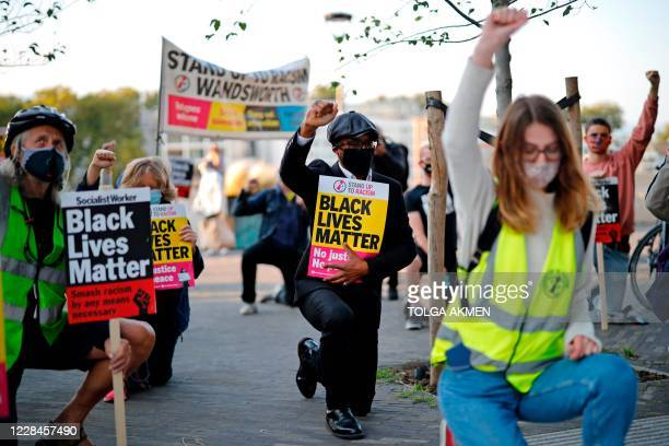 Protesters from Black Lives Matter take a knee as they gather outside the US Embassy in London on September 11 the day of a trial hearing of the four...